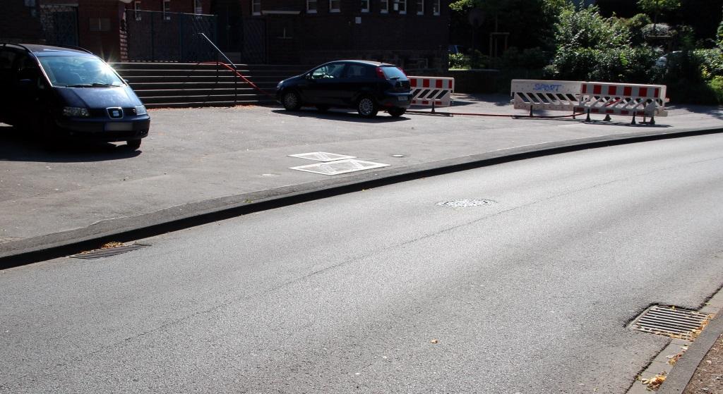 Links und recht am Straßenrand führen die Abläufe wie gehabt Wasser in den Kanal ab. Mitten auf der Adolf-Clarenbach-Straße stellt einer weiterer Ablauf sicher, dass sich im Starkregenfall kein Wasser mehr mitten auf der Straße sammeln kann. (Foto: B. Glumm)