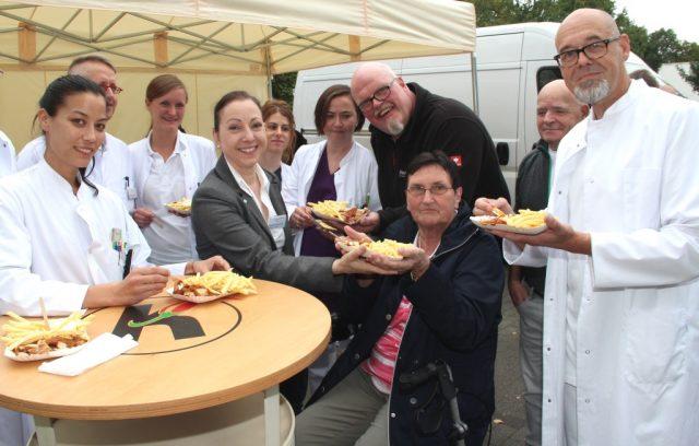 Erika Kempner (77, sitzend) kam im Juni mit einer schweren Lungenentzündung ins St. Josef Krankenhaus in Hilden. Sohn Martin (3.v.r.) bedankte sich jetzt bei den behandelnden Ärzten und dem Pflegepersonal mit Currywurst und Pommes. Darüber freute sich nicht nur Krankenhaus-Direktorin Monika Felkl (4.v.li.). (Foto: B. Glumm)