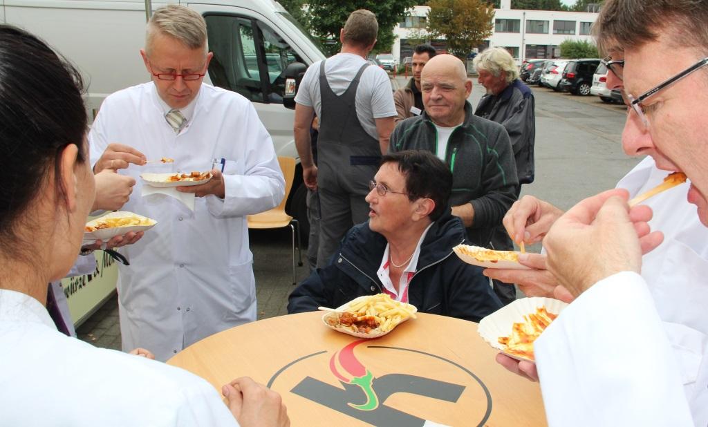 Erika Kempner genoß Montagmittag gemeinsam mit ihren ehemailgen Ärzten und Pflegern vor dem St. Josef Krankenhaus in Hilden eine deftige Currywurst. (Foto: B. Glumm)