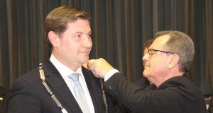Bürgermeister Ernst Lauterjung (SPD) legt Tim Kurzbach die Amtskette des Oberbürgermeisters um. Vereidigt wurde der 38-Jährige am 29. Oktober letzten Jahres im der Ohligser Festhalle. (Archivfoto: B. Glumm)