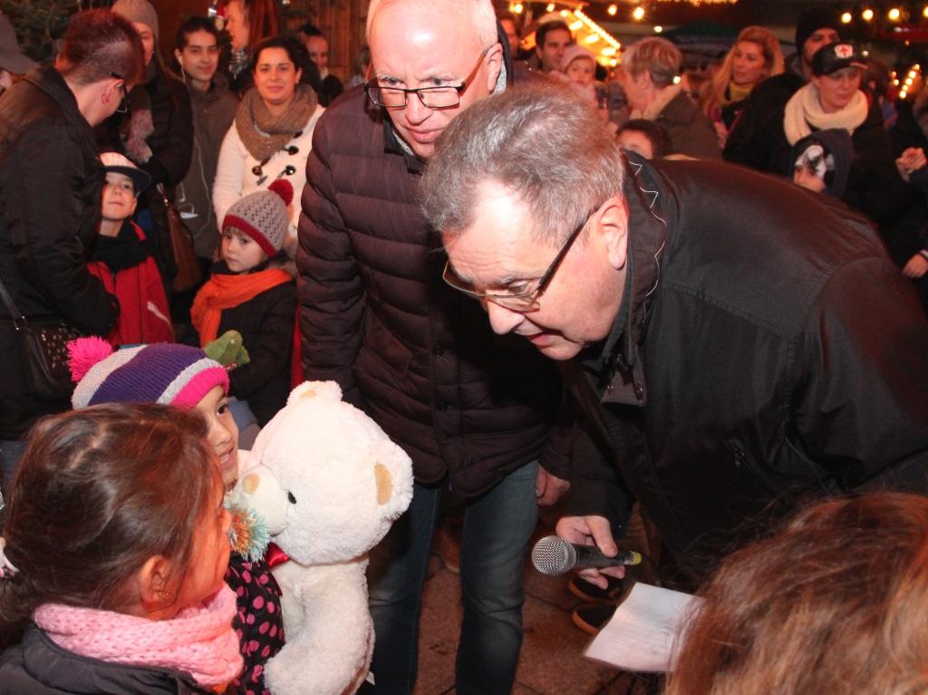 Bürgermeister Ernst Lauterjung (re.) und Detlef Ammann von der W.I.R. hatten am Montag alle Hände zu tun, als sie die vielen Kinder der anwesenden Kitas für ihre toll geschmückten Weihnachtsbäume belohnten. (Foto: B. Glumm)