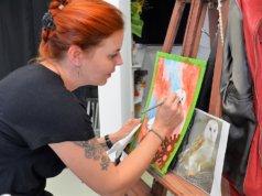 Bei der Vernissage führt Alexandra Keller live eine Airbrush-Arbeit vor. Nach dem Aufsprühen wird die Farbe partiell wieder entfernt, um anschließend mit Künstlerbuntstiften Akzente zu setzen. (Foto: © Martina Hörle)