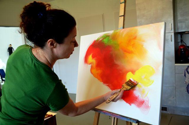 Silke Widenka experimentiert gerne mit Materialien, kombiniert Malstile. Hier trägt sie mit breitem Pinsel Acrylfarbe in geschwungenen Bahnen auf.(Foto: © Martina Hörle)