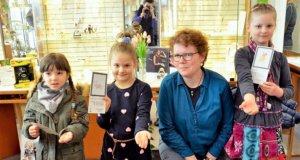 Die kleinen Malkünstlerinnen nehmen ihre Gewinne strahlend entgegen. Frauke Pohlmann hat die Hasenbilder in zauberhafte silberne Kettenanhänger umgesetzt. (v. li.: Valerie (5), Carolina (6), Goldschmiedin Frauke Pohlmann, Isa (8) (Foto: © Martina Hörle)