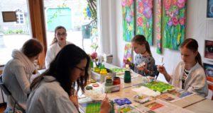 Die fünf jungen Malerinnen im Alter von 10 – 14 Jahren sitzen mit großer Begeisterung an ihrer Arbeit. Alle sind stolz darauf, an diesem großen Gemeinschaftswerk mitzuarbeiten. (Foto: © Martina Hörle)