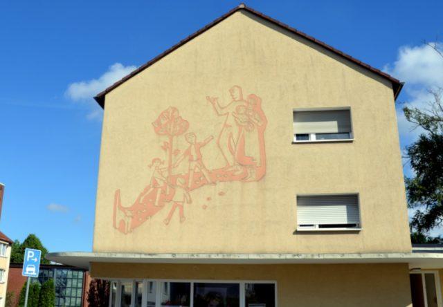 Diese Hausfassade in der Niibelungensiedlung wurde 1957 von Lies Ketterer direkt vor Ort gestaltet. Es zeigt eine harmonische Szene mit den für die Künstlerin typischen Motiven. (Foto: © Martina Hörle)