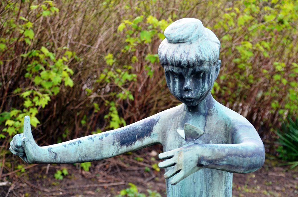 Staunend betrachtet das Mädchen einen kleinen Schmetterling. Entstanden ist die Figur 1963. Im gleichen Jahr wurde der Botanische Garten eingeweiht. (Foto: © Martina Hörle)