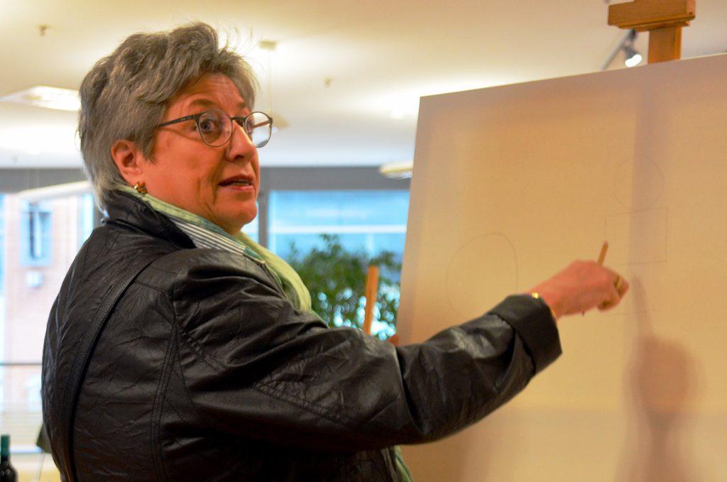 Sylvia Heinrichs-Reinshagen, die Leiterin der Stadtbibliothek, greift als Erste zum Bleistift. Für das Aktionsbild soll aus Kreisen, Dreiecken und Vierecken ein Gesamtwerk entstehen. (Foto: © Martina Hörle)