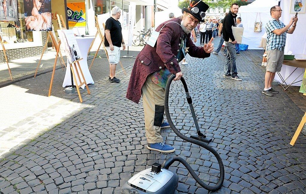 Lothar Ruthmann von der Galerie Ruthmann sorgte für Sauberkeit. Mit einem Staubsauger wanderte der surrealistische Künstler über die Grünstraße. (Foto: © Martina Hörle)