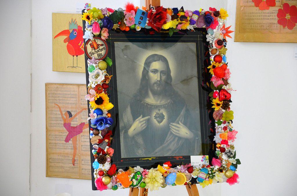 """Sabine Schott hat mit ihrem Bild von Jesus in einem bunt verzierten Rahmen einen starken Kontrast geschaffen. """"Rosen, Herzen, Obst sind Natur, sind Leben"""", sagt sie. """"Jesus ist auch Leben."""" (Foto: © Martina Hörle)"""