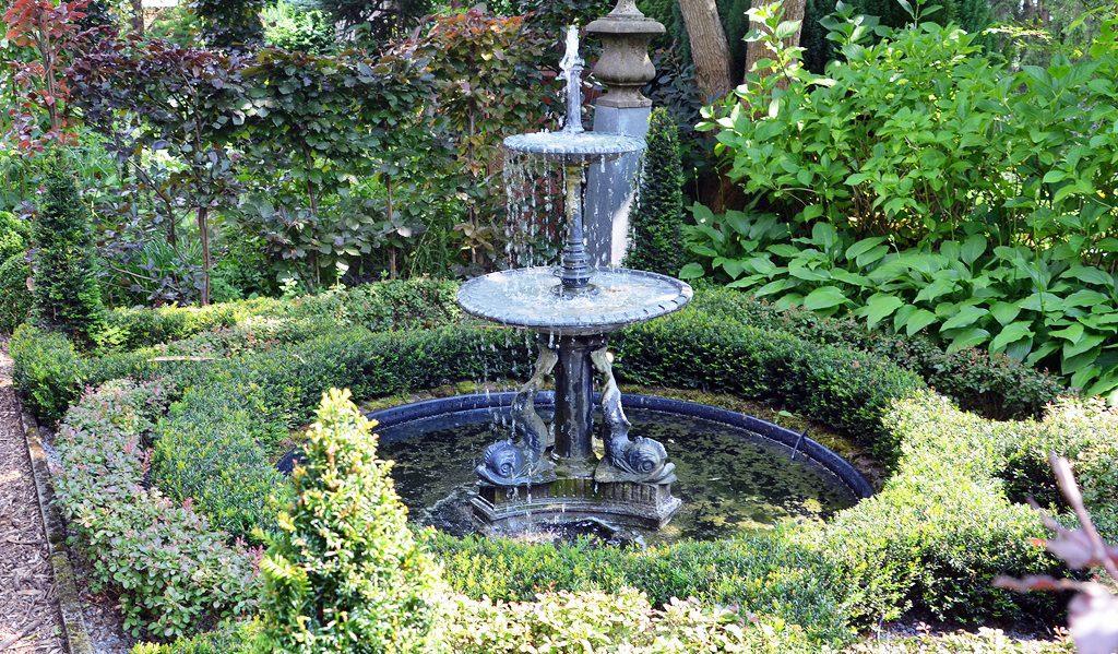 Im Knotengarten plätschert ein kleiner Springbrunnen. Der Sockel wird von steinernen Fischen gehalten. Der Knotengarten war das zweite Gartenzimmer. Angefangen hatte alles mit dem Teichgarten. (Foto: © Martina Hörle)
