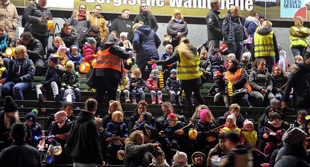 Auf der Bühne versammelten sich die vielen Besucher, um von dort aus die Szene der Mantelteilung zu sehen. Gemeinsam wurden Martinslieder gesunden. Im Anschluss gab es 1.800 Weckmänner für die Kinder. (Foto: © Martina Hörle)
