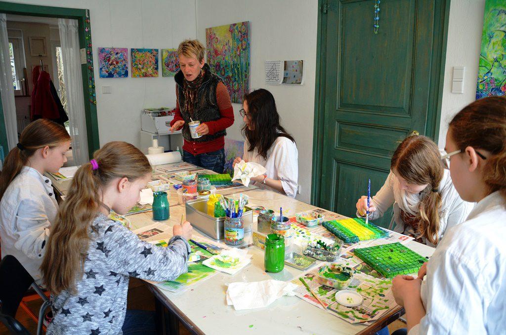 Heike Buschkotte-Leichsenring hat gute Tipps für die eifrigen Malerinnen parat. Hier erläutert sie gerade das Deckergebnis der Farbe Gelb. (Foto: © Martina Hörle)
