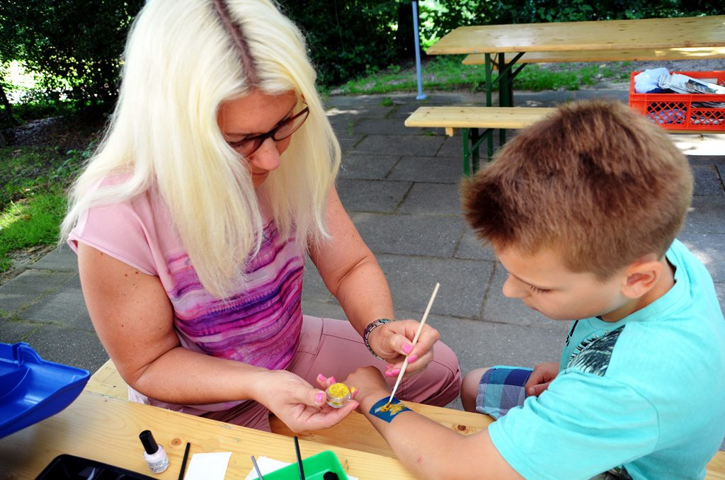 Der neunjährige Ben hat sich gekreuzte Schwerter als Tattoo ausgesucht. Mutter Nicole von Werne trägt goldenes Glitzerpulver auf. (Foto: © Martina Hörle)