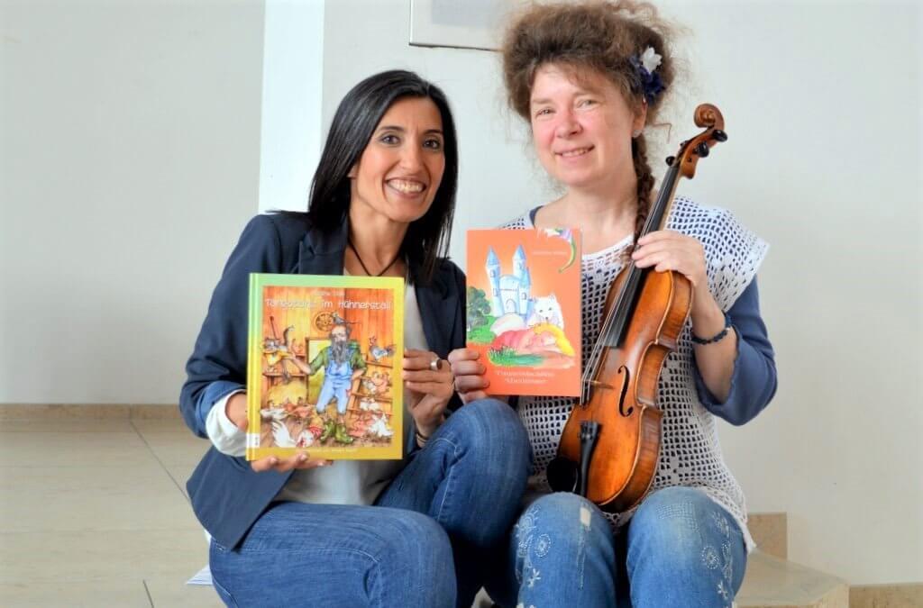 """In der Kulturwoche gibt es auch ein Kinderprogramm. Es wird aus den Kinderbüchern """"Tangotanz im Hühnerstall"""" und """"Tausendschöns Abenteuer"""" gelesen. (Fotografin Maryam Sabri (li.) zeigt das Buch von Nadine Diab. Andrea Daun liest aus ihrem Buch und sorgt mit der Geige für die musikalische Untermalung) (Foto: © Martina Hörle)"""