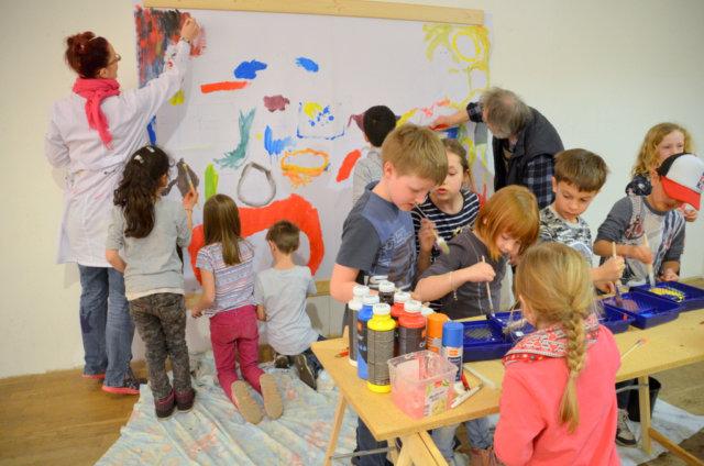 Gemeinsam mit den Künstlern Saskia Bela und Lothar Ruthmann gestalteten die Kinder der Grundschule Schützenstraße ein fröhliches und buntes Gemeinschaftswerk, das in Kürze auf dem Ferien(s)pass-Plakat zu sehen sein wird. (Foto: © Martina Hörle)