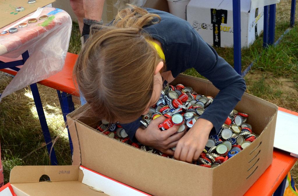 Bei dem Gesamtkunstwerk waren alle Kinder eifrig bei der Sache. Und wenn man einen ganz bestimmten Kronkorken sucht, muss man schon mal tiefer graben. (Foto: © Martina Hörle)