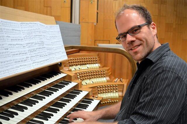 Der Dipl.-Kirchenmusiker Mathias Staut ist neuer Chorleiter des Solinger Theaterchors. Hier probiert er vor der ersten Probe die Orgel aus. (Foto: © Martina Hörle)