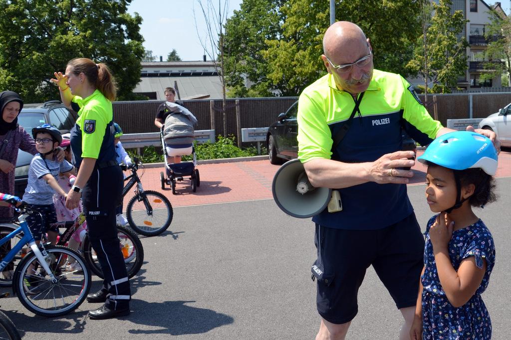 Verkehrssicherheitsberater Ulrich Schmidt zeigt Kindern und Eltern, was man bei einem Fahrradhelm beachten muss. (Foto: © Martina Hörle)