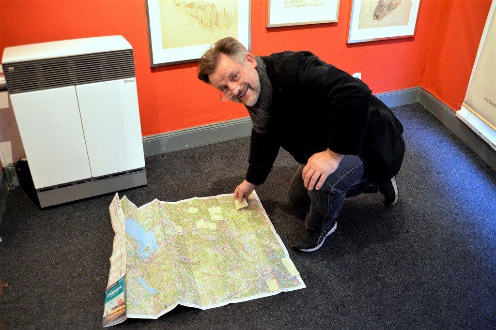 Mit Hilfe einer Karte vom Chiemgau versucht Galerist Balke akribisch, die Wanderungen von de Leuw nachzuvollziehen. (Foto: © Martina Hörle)