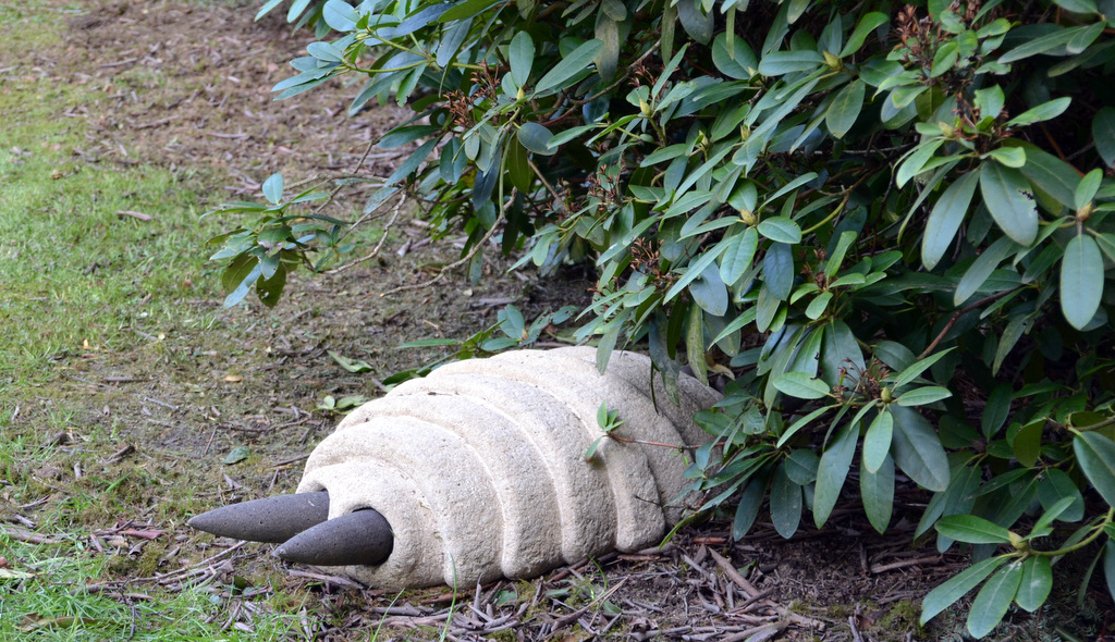 Versteckt unter einem Busch schaut ein Wesen aus Kalkstein mit Basaltlava hervor, das an ein Insekt erinnert. (Foto: © Martina Hörle)
