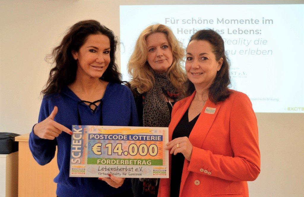 Petra Rottmann (re.) von der Deutschen Postcode-Lotterie übergibt symbolisch den Scheck über 14.000 Euro an Schirmherrin Mariella Ahrens (li.) und Geschäftsführerin Petra Krötzsch (Mitte) vom Verein Lebensherbst. (Foto: © Martina Hörle)