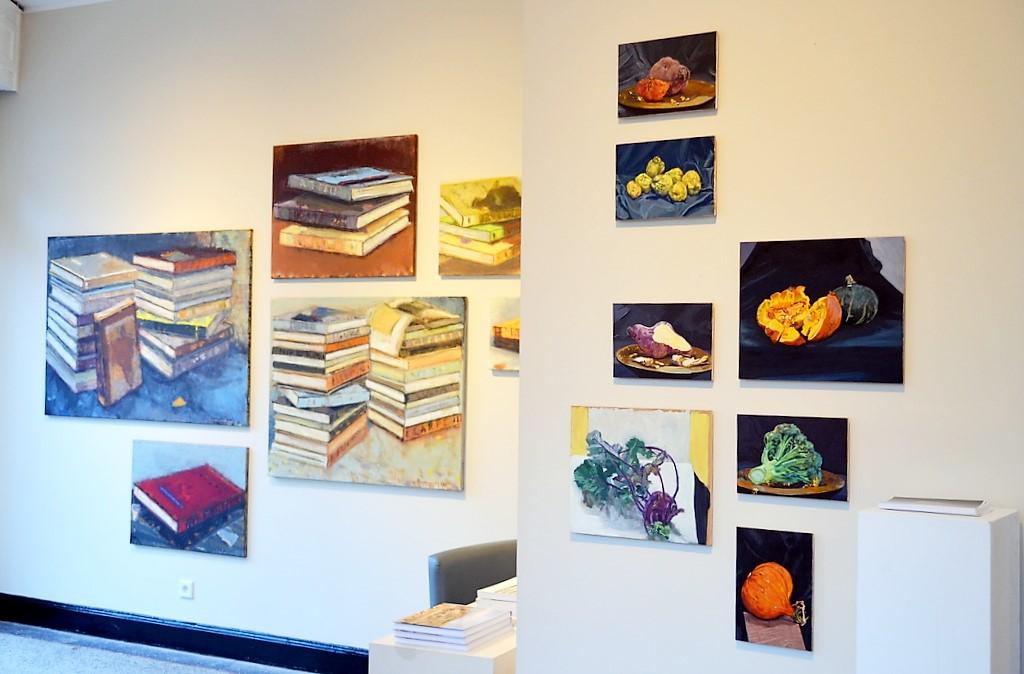 Im Vordergrund rechts sieht man Werke des Amsterdamer Künstlers Rudolf Valster. Er arbeitet häufig mit Motiven aus dem Lebensmittelbereich, die er dann im Großformat darstellt. Links sind Ioan Iacobs Darstellungen zu sehen. Mal sind Bücher als Einzelobjekt zu sehen, dann wieder zu Türmen aufgebaut. (Foto: © Martina Hörle)