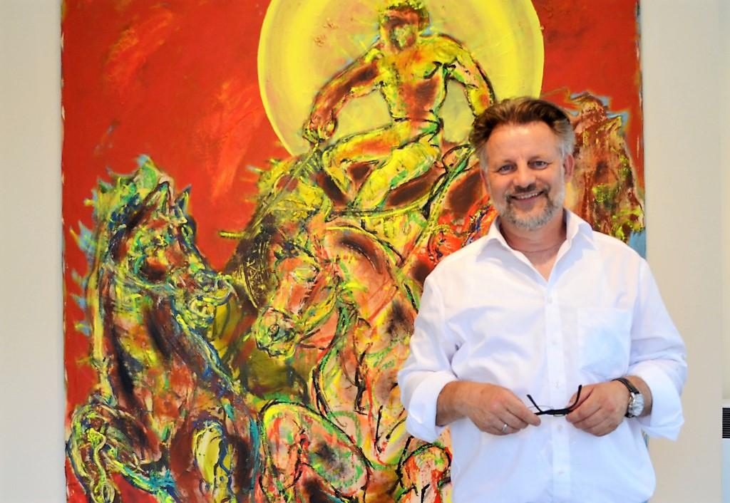 Dirk Balke freut sich auf die neue Ausstellung der Galerie ART-ECK. Im Hintergrund ist eine Darstellung des Sonnengottes zu sehen, ein Werk des Künstlers Eckart Boese. (Foto: © Martina Hörle)