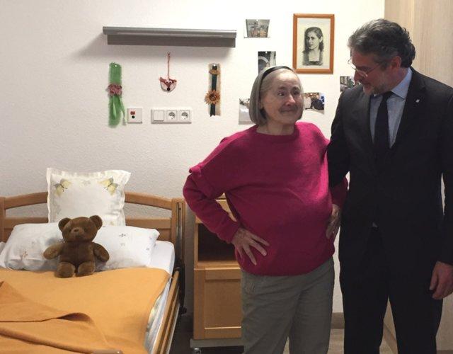 Inge Widowsky fühlt sich in ihrem neuen Zimmer im St. Lukas Pflegeheim sichtlich wohl. Franziskus von Ballestrem, Bereichsdirektor für die Senioreneinrichtungen der Kplus Gruppe, besucht die langjährige Bewohnerin in ihrem neuen Zuhause. (Foto: © Kplus Gruppe)