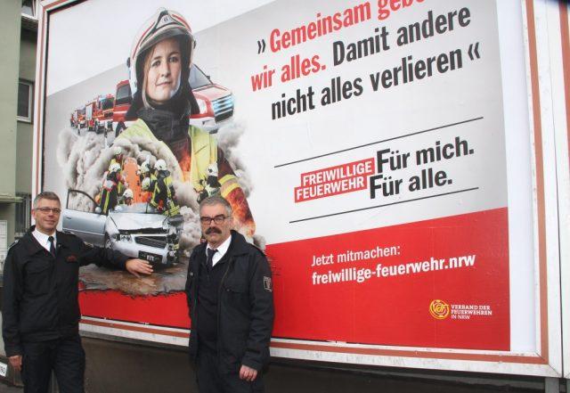 Landesweit wird großflächig um Nachwuchs für die Einheiten der Freiwilligen Feuerwehr geworben. Torsten Dunkel (li.) und Hans-Joachim Krapp von der Solinger Feuerwehr stellten die Kampagne am Plakatstandort in Aufderhöhe vor. (Foto: © B. Glumm)
