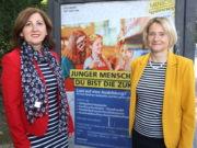 Maria Ricchiuti (li.) und Kristin Degener vom Kommunalen Jobcenter vor einem City-Light-Poster der Kampagne. Die Poster sind seit Dienstag an Bushaltestellen im Stadtgebiet angebracht. (Foto: © Bastian Glumm)