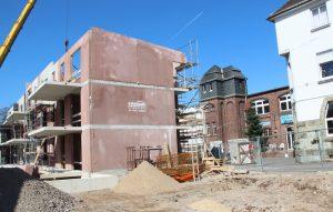 """Auf der linken Seite des Carrés entstehen drei Neubauten, zwei sind bereits im Rohbau zu sehen. Dort wird barrierefreies Wohnen möglich sein. Auf der rechten Seite werden Bestandsbauten der alten Papierfabrik saniert und in """"normalen"""" Wohnraum umgewandelt. (Foto: © B. Glumm)"""