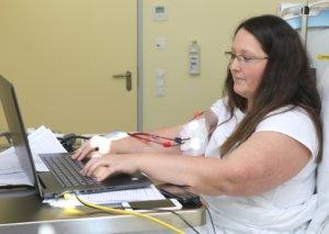 Carina Seidler kann ihre Aufgaben während der Dialyse vollumfänglich wahrnehmen. Dazu wurde eigens ein Arbeitsplatz ans Krankenbett angepasst. (Foto: © Bastian Glumm)