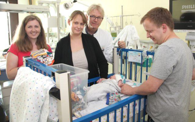 Eva Linder (li.) überreichte am Donnerstag 57 selbstgenähte Mützen für die ganz kleinen Patienten auf der Frühgebornenenstation im Klinikum. Der kleine Joshua (vier Tage alt) bekam das erste Exemplar. Mutter Maike Rieke (2.v.li.) und Vater Matthias (re.) freuten sich ebenso, wie Dr. Volker Soditt, Chefarzt der Klinik für Kinder und Jugendliche am Klinikum Solingen. (Foto: © B. Glumm)