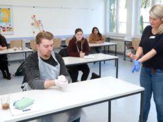 Hygiene-Ausbilderin Ramona Wiefers zeigt Pascal Wilke (Lukas Pflegeheim) erste Griffe beim Anlegen der Handschuhe. (Foto: © Kplus Gruppe)
