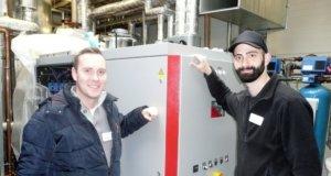 Patrick Preiss (li.), Energiemanager der Technischen Abteilung der Kplus Gruppe, und Kemal Hilmi Dogan, Technischer Betriebsleiter der Genesis Zentralküche an der Alsenstraßen, vor dem 2017 dort installierten neuen Blockheizkraftwerk. (Foto: © Kplus Gruppe)