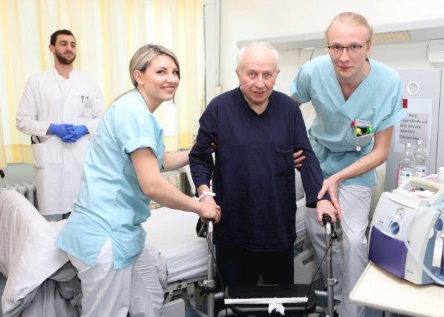 Hermine Harder (li.) und Philipp Röltgen (re.) helfen einem Patienten der St. Lukas Klinik. Im Hintergrund Assistenzarzt Tariq Al-Hindi. (Foto: © Kplus Gruppe)