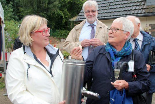 PHoS-Vorsitzende Cordula Scheffels (li.) sammelte gestern kleine symbolische Geschenke in einer Metalldose, die demnächst im Innenhof des Hospizneubaus vergraben wird. Auch Sabine Schulz-Wolff von der Stiftung Botanischer Garten hatte eine Kleinigkeit dabei. PHoS-Vorstandsmitglied Ludger Hoebink schaute den Damen über die Schultern. (Foto: © B. Glumm)