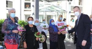 Strahlende Gesichter unter den Mund-Nasen-Masken: Raoul Brattig (re., FDP) bedankte sich bei der Belegschaft der Evangelischen Altenhilfe Wald jetzt mit Blumen. (Foto: © Bastian Glumm)